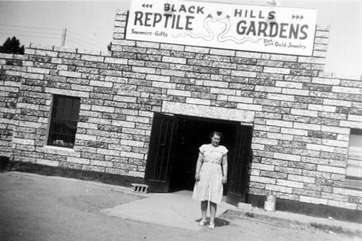 A historic black and white photo of a lady standing in front of the Black Hills Reptile Gardens entrance in 1937.